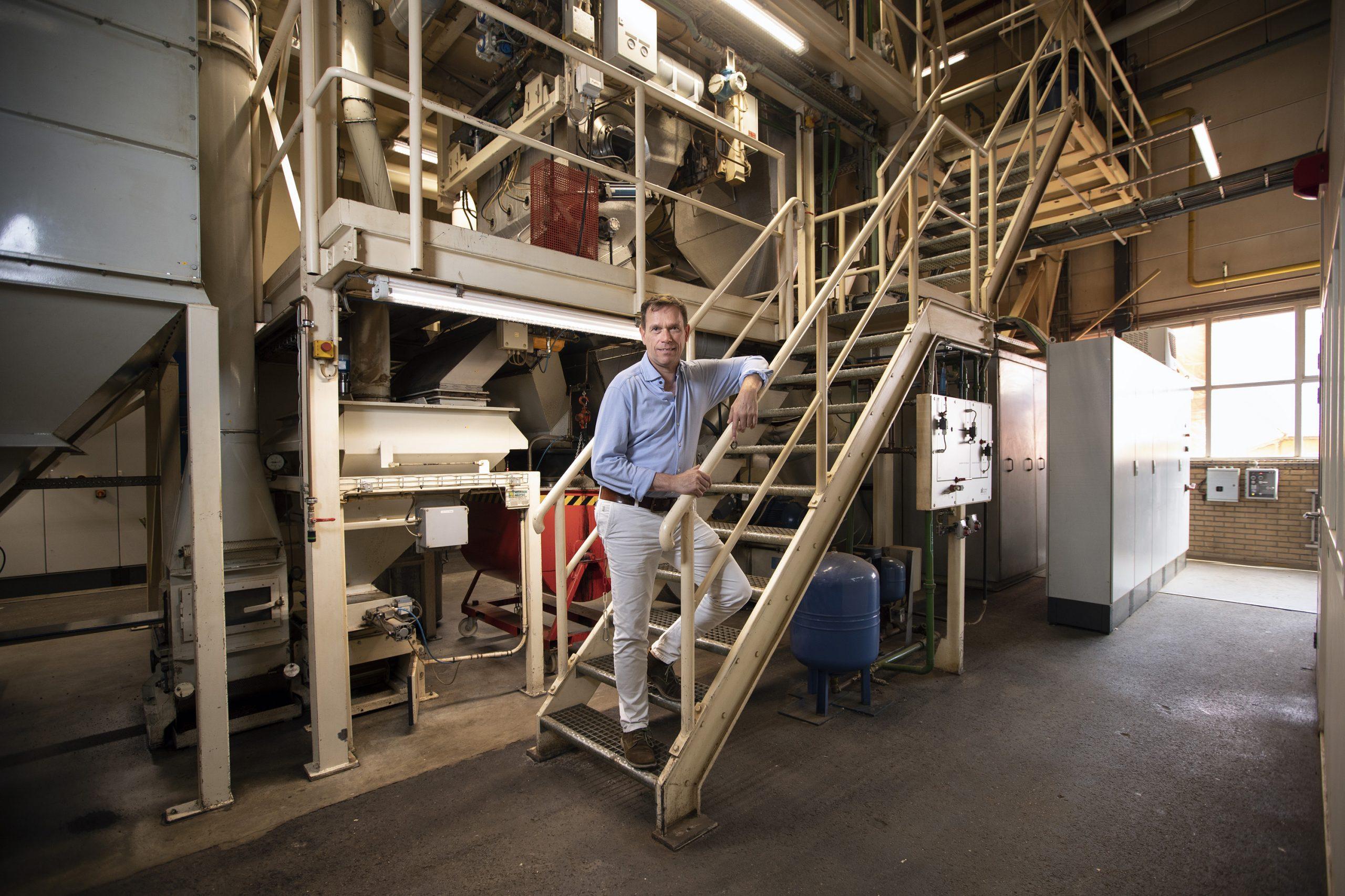 Guido van As op stalen trap in zijn loods