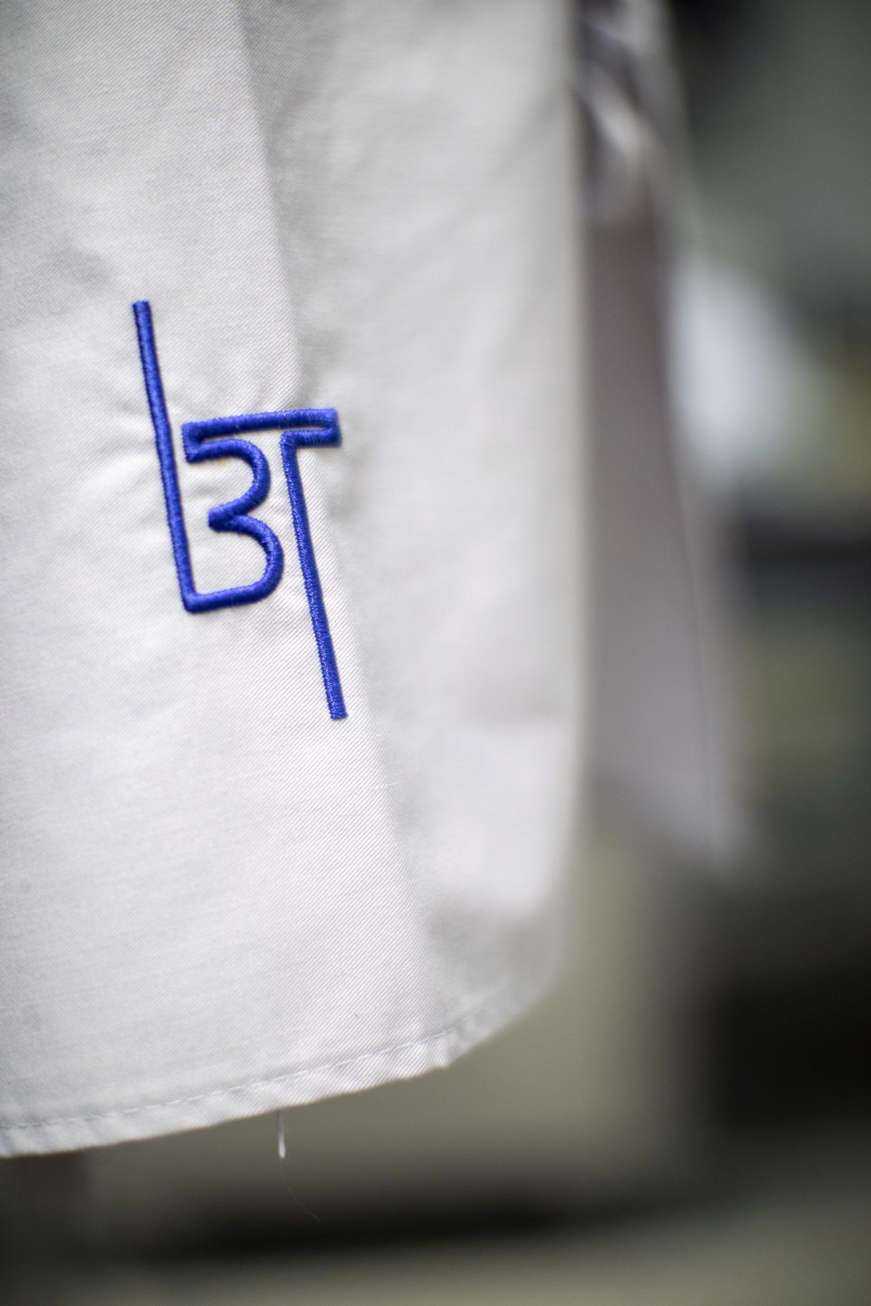Het monogram van Tol op de kleding, blauw getint