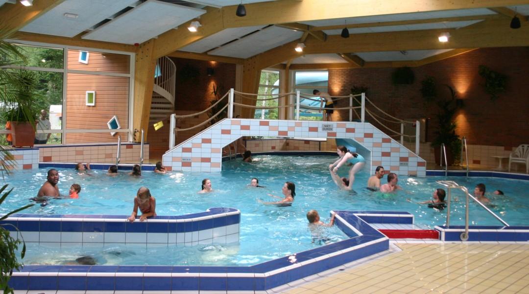 Foto van het binnenzwembad van de camping, vol met spelende kinderen.
