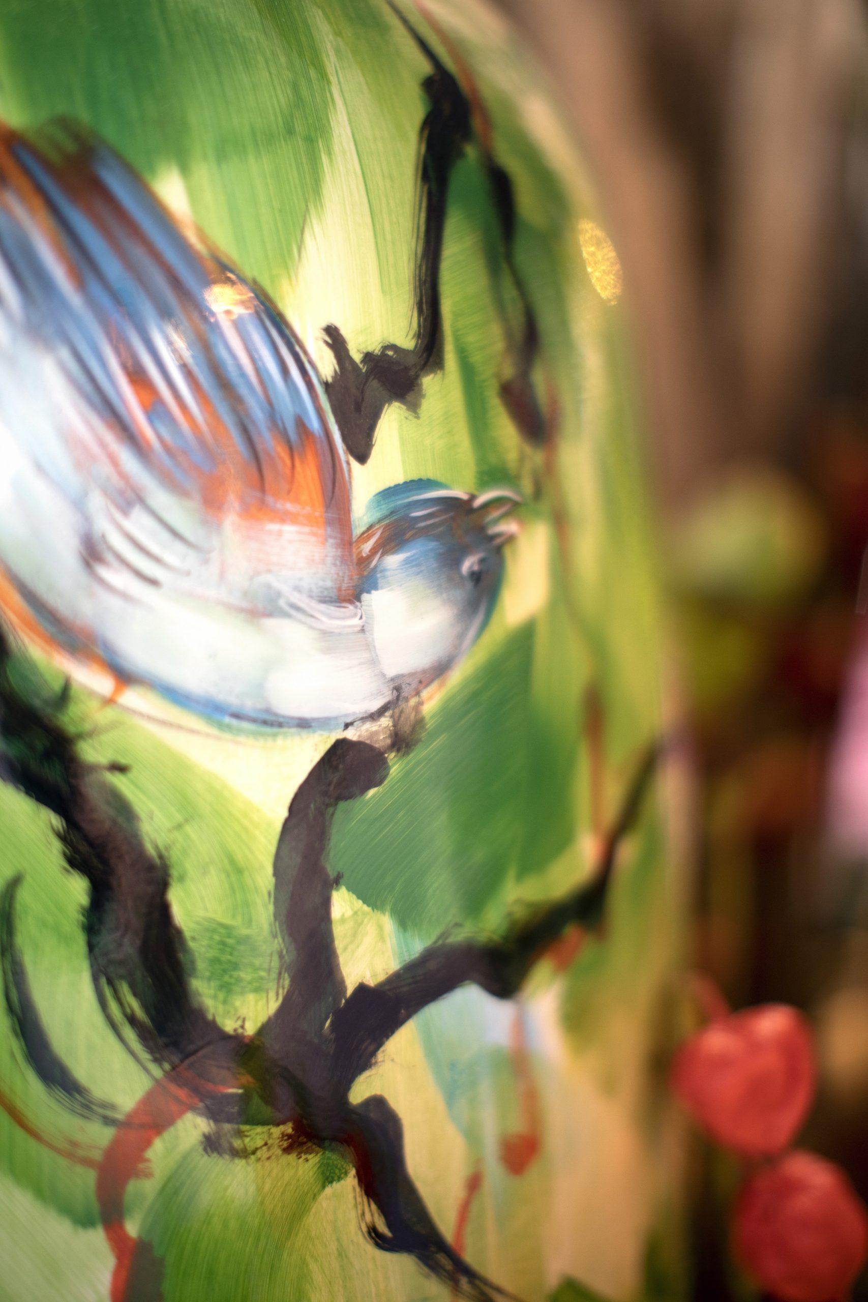 Een glas beschilderde vaas met een vogel als afbeelding