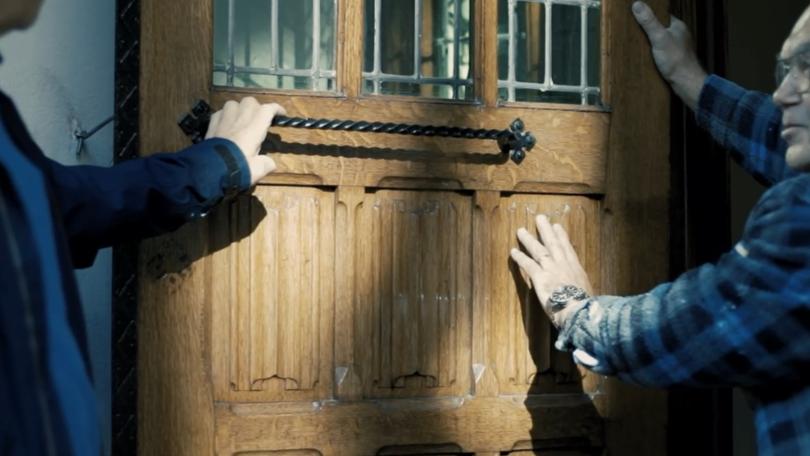 Twee schilders die het verfwerk van een kloosterdeur bevoelen