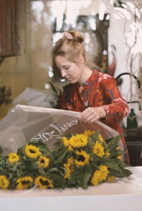 Loes Smeets die een boeket zonnebloemen inpakt