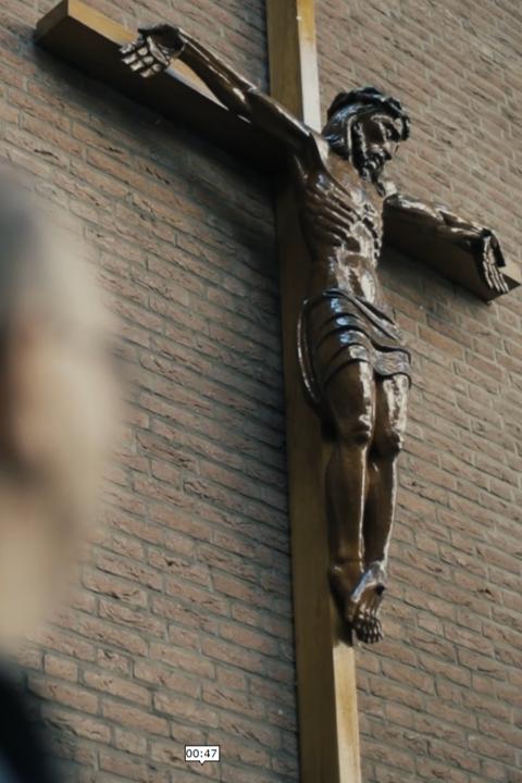 De heer Schefman kijkend naar het kruis met Jezus daar op, nu het Jezusbeeld scherp