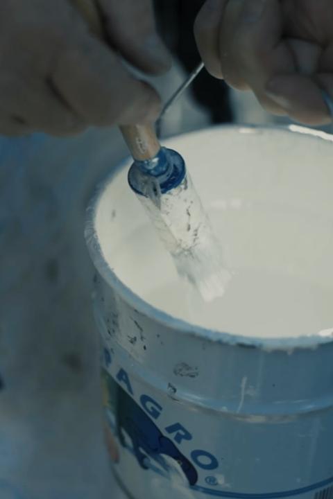 kwast die in een verfpot wordt gedoopt, witte verf