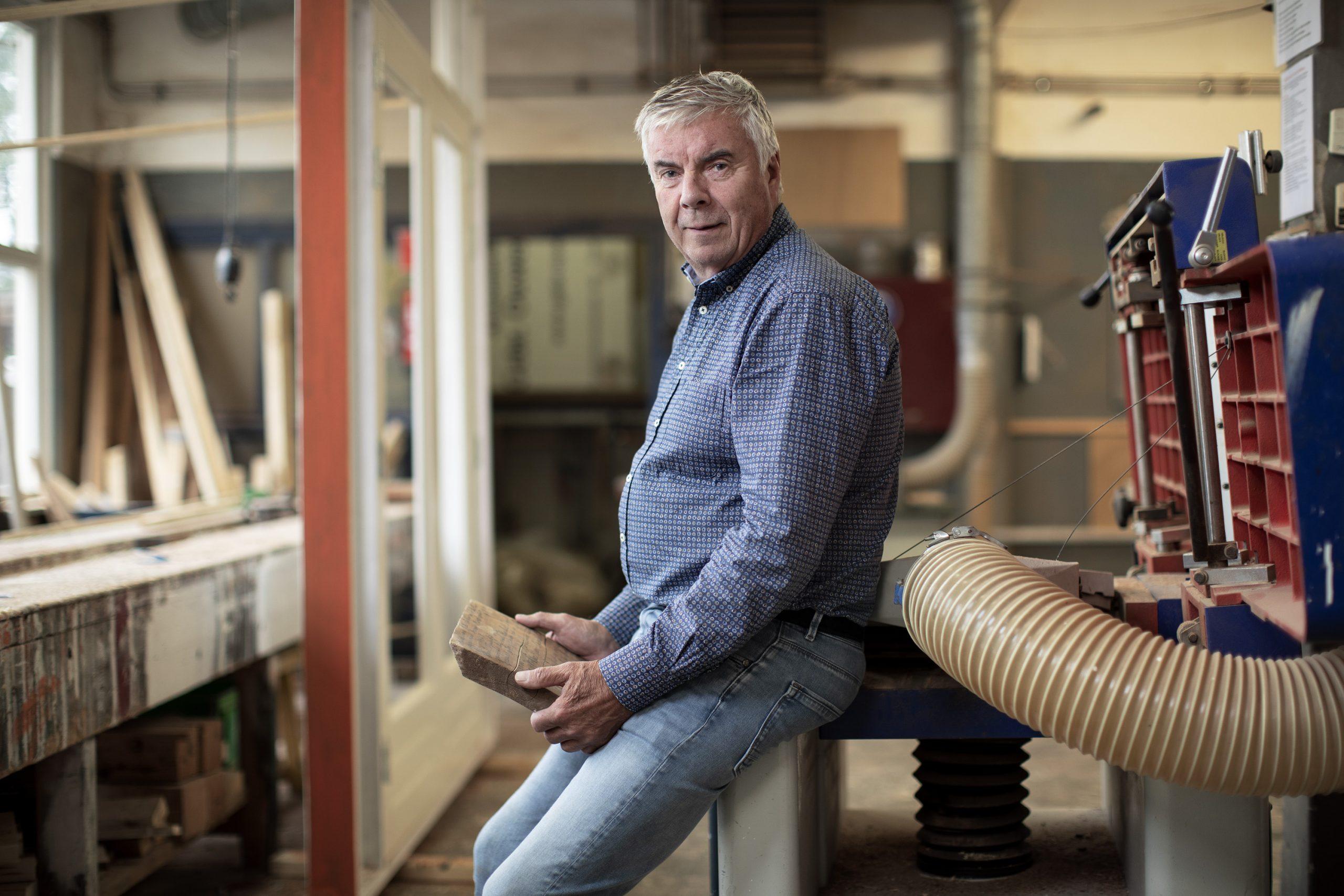 Kees Ouwendijk zittend op zijn werkbank in de werkplaats