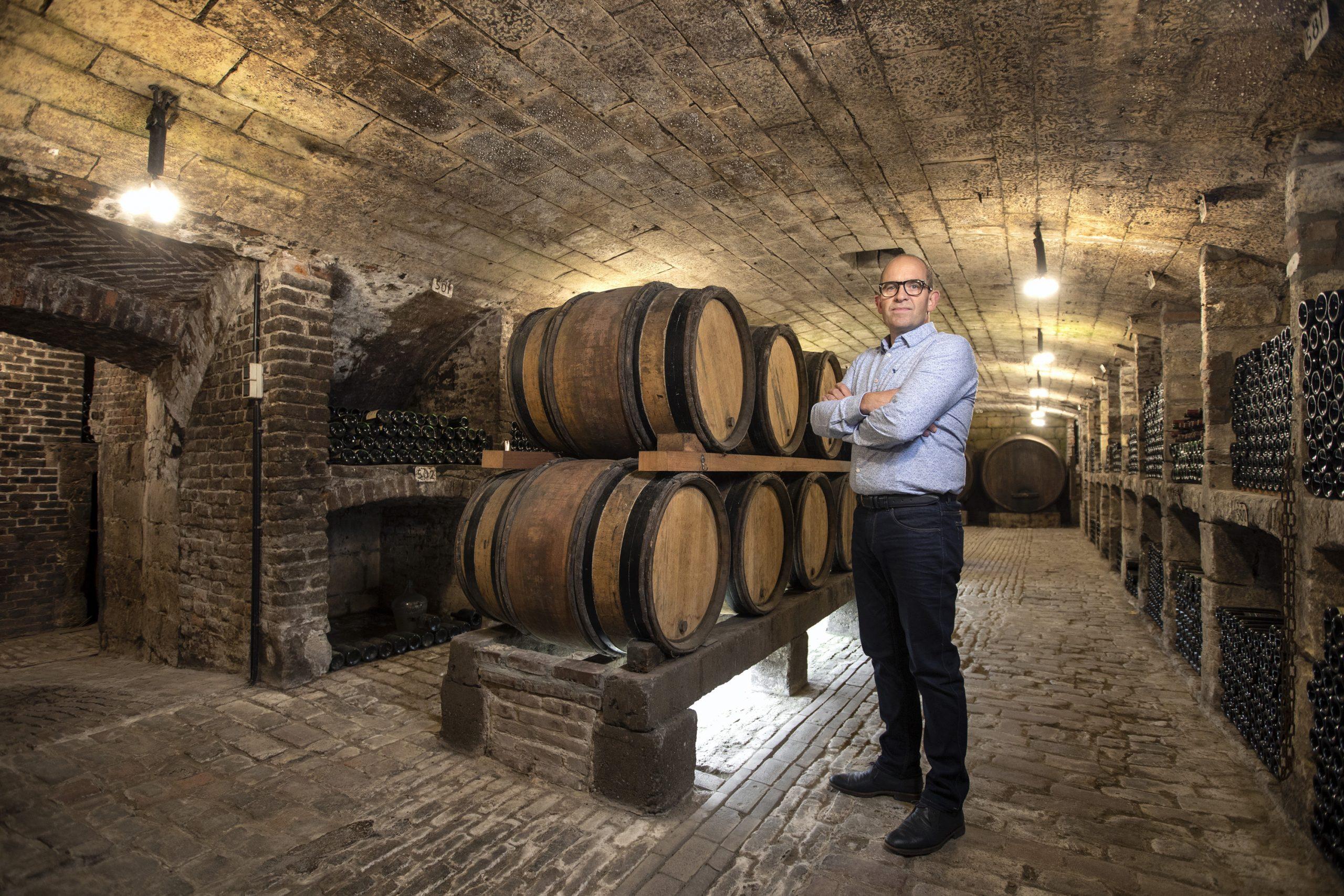 Gerry Habets staand tussen de wijnvaten in zijn kelder